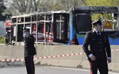 FILE: Italian policemen work by the wreckage of a school bus that was transporting some 50 children on 20 March 2019 after it was torched by the bus' driver, in San Donato Milanese, southeast of Milan. Picture: AFP