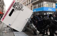FILE: Demonstrators overturn a container during a demonstration against the pension overhauls, in Paris, on 5 December 2019 as part of a nationwide strike. Trains cancelled, schools closed: France scrambled to make contingency plans on for a huge strike against pension overhauls that poses one of the biggest challenges yet to French President's sweeping reform drive. Picture: AFP.