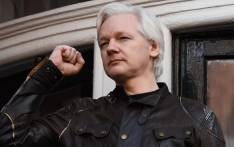 In this file photo taken on 19 May 2017, Wikileaks founder Julian Assange raises his fist prior to addressing the media on the balcony of the Embassy of Ecuador in London. Picture: AFP.