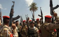 FILE: Iraqi army troops chant slogans against the Islamic State of Iraq and the Levant (ISIL) as they recruit volunteers to join the fight against a major offensive by the jihadist group in northern Iraq, outside a recruiting centre in the capital Baghdad on 13 June 2014. Picture: AFP.