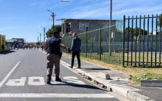 A Cape Town Metro Police officer (left) directs Langa residents to remain indoors during the coronavirus lockdown on 27 March 2020. Picture: Kaylynn Palm/EWN