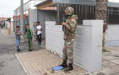 A group of boys look on as a SANDF soldier patrols the area, during an operation in Manenberg. Picture: Bertram Malgas/EWN