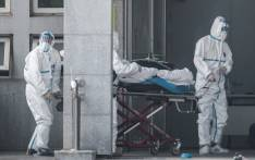 Medical staff members carry a patient into the Jinyintan hospital, where patients infected by a mysterious SARS-like virus are being treated, in Wuhan in China's central Hubei province on 18 January 2020. Picture: AFP