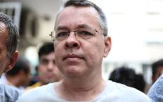In this file photograph taken on 25 July 2018, US pastor Andrew Craig Brunson is escorted by Turkish plain clothes police officers to his house in Izmir. Picture: AFP