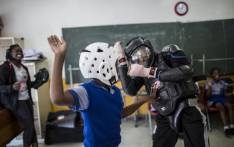 Girls practice self-defence methods on an instructor dressed in protective gear during a session with NGO Action Breaks Silence (ABS) called 'Empowerment through self-defence for women and girls' which aims to create a world free from fear of gender-based violence, on 10 October 2018 at Mbuyisa Makhubu Primary School in Soweto. Picture: AFP.