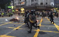 Hong Kong police advance down a road during clashes with protesters in the Wanchai district in Hong Kong on 6 October 2019. A Hong Kong judge on October 6 rejected a challenge to an emergency law criminalising protesters wearing face masks as democracy activists hit the streets again in defiance of the ban despite half the city's subway stations remaining closed. Picture: AFP