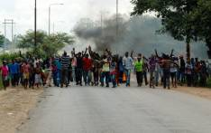 Angry protesters gesture as they block the main route to Zimbabwe's capital Harare from Epworth township on 14 January 2019 after announced a more than hundred percent hike in fuel prices. Picture: AFP