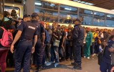 Law enforcement officers help keep order as commuters board a bus following a protest near the Cape Town bus terminal after taxi operators were arrested for outstanding warrants on 15 October 2019. Picture: Kaylynn Palm/EWN