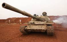 A Syrian rebel-fighter from the National Liberation Front (NLF) secures a tank, part of heavy weapons and equipment withdrawn on 8 October 2018 from a planned buffer zone around Idlib in one of the group's rear positions in a rebel-held area in the south-western Syrian province. Picture: AFP.