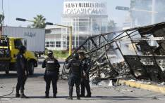 Policemen stand next to a burnt vehicle after heavily armed gunmen waged an all-out battle against Mexican security forces in Culiacan, Sinaloa state, Mexico, on 18 October 2019. Picture: AFP