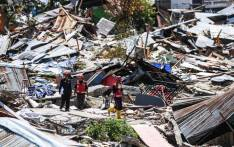 Rescuers walk past debris at Perumnas Balaroa village in Palu, Indonesia's Central Sulawesi on 5 October 2018, following the 28 September earthquake and tsunami. Picture: AFP