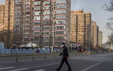 A man wearing a protective mask walks along an empty street in Beijing on 31 January 2020, following a SARS-like virus outbreak which began in the Chinese city of Wuhan. Picture: AFP