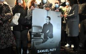Relatives and colleagues hold a picture of Samuel Paty during the 'Marche Blanche' in Conflans-Sainte-Honorine, northwest of Paris, on 20 October 2020, in solidarity after he was beheaded for showing pupils cartoons of the Prophet Muhammad. Picture: AFP