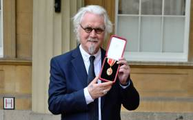 FILE: British comedian Billy Connolly poses with his medal after being knighted as a Knights Bachelor (knighthood) for services to entertainment and charity during an investiture ceremony at Buckingham Palace, London on 31 October 2017. Picture: AFP