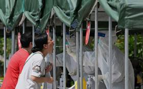 FILE: A health worker takes a swab sample from a woman to be tested for the COVID-19 coronavirus at a nucleic acid sample collection station at a park in Beijing on 5 August 2021. Picture: Noel Celis/AFP