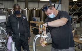 Brewer Julian Pienaar, 44, checks a new keg before starting bottling cans with beer at the Hops End Brewery in Benoni, South Africa, on 14 January 2021. Picture: AFP