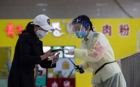 A staff member (R) wearing a face shield talks with a passenger at a long-distance bus station in Wuhan in China's central Hubei province on 30 April 2020. Picture: AFP