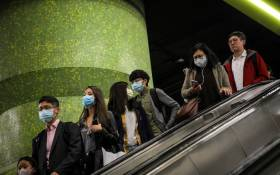 Commuters wearing face masks as a precautionary measure to protect against the possible spread of a SARS-like virus outbreak ride an escalator at an MTR subway station ahead of the Chinese New Year in Hong Kong on 23 January 2020. Picture: AFP