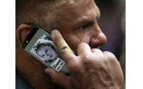 Former soccer player Marc Batchelor speaks on his mobile phone adorned with a photo of Reeva Steenkamp, at the sentencing of South African Paralympic athlete Oscar Pistorius at the High Court in Pretoria, in October 2014. Picture: AFP.