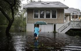 Kim Adams makes her way to her home that is surrounded by flood waters after Hurricane Florence passed through the area on September 15, 2018 in Southport, North Carolina. Picture: AFP.