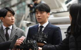 Seungri (C), a member of the K-pop boy group BIGBANG, speaks to the media as he arrives for questioning over criminal allegations at the Seoul Metropolitan Police Agency in Seoul on 14 March 2019. Picture: AFP.