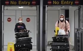 In this file photo taken on 8 June 2020 passengers wearing PPE (personal protective equipment), including a face mask as a precautionary measure against COVID-19, arrive at Terminal 1 of Manchester Airport in north west England. Picture: AFP
