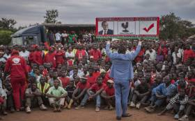 A supporter of Lazarus Chakwera, leader of the Malawi Congress Party (MCP), the main Malawi opposition party, holds a sign during a campaign rally at Chowo Primary school in Lilongwe on 12 May 2019, ahead of Malawi's general election. Picture: AFP.