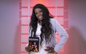 Internationally accredited money coach and author Busi Selesho seen with her book 'Money and Black People' Picture: Ihsaan Haffejee/EWN