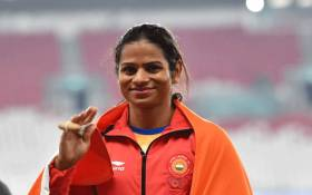 Silver medallist India's Dutee Chand celebrate during the victory ceremony for the women's 100m athletics event during the 2018 Asian Games in Jakarta on August 26, 2018. Picture: AFP.