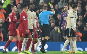 Referee Craig Pawson (C) books Manchester United goalkeeper David de Gea (3R) for dissent during the English Premier League football match between Liverpool and Manchester United at Anfield in Liverpool, north-west England on 19 January 2020. Picture: AFP