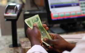 A man holds bond notes released by the Reserve Bank of Zimbabwe in Harare central business centre on 28 November 2016. Picture: AFP.