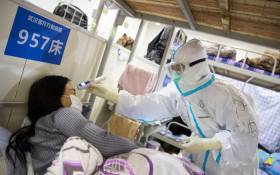 This photo taken on 17 February 2020 shows a member of the medical staff (L) checking the body temperature of a patient who has displayed mild symptoms of the COVID-19 coronavirus, at an exhibition centre converted into a hospital in Wuhan in China's central Hubei province. Picture: AFP