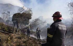 Fire-fighting teams dampen smouldering vegetation, finally getting a fierce forest fire under control on the foothills of Table Mountain in Cape Town on 19 April 2021. 