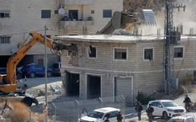 This picture taken from the West Bank on 22 July 2019 shows Israeli security forces tearing down one of the Palestinian buildings still under construction which have been issued notices to be demolished in the Wadi al-Hummus area adjacent to the Palestinian village of Sur Baher in East Jerusalem. Picture: AFP