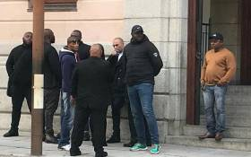 Nafiz Modack, pictured wearing a white shirt and black coat, is surrounded by security personnel outside the Cape Town Regional Court on 16 April 2019. Picture: Shamiela Fisher/EWN