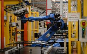 FILE: A robot arm carries a glass part in the assembly line of a factory. Picture: AFP