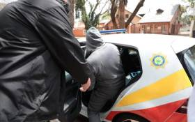 Hawks members arrest a suspect on 30 September 2020 in a case related to a R255m asbestos removal project in Free State. Picture: Abigail Javier/EWN