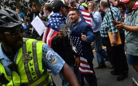 Police escort 'Unite the Right' organizer Jason Kessler (C) and protestors during a far-right rally at Lafayette Park opposite the White House 12 August, 2018 in Washington, DC, one year after the deadly violence at a similar protest in Charlottesville, Virginia. Picture: AFP