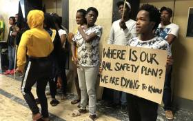 A protester holds a placard outside the Prasa offices in Cape Town on 17 April 2019. Picture: Kaylynn Palm/EWN.