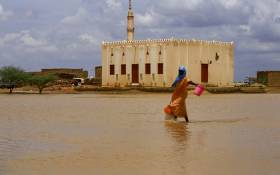 FILE: A Sudanese woman crosses a flooded area, as a result of flooding and torrential rain, in the town of Osaylat, 50 km southeast of the capital Khartoum, on August 6, 2020. Picture: Ashraf Shazly / AFP.