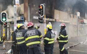 Firefighters attend to a burning building on the corner of De Villiers and Rissik street in Johannesburg. Picture: Kgothatso Mogale/EWN.