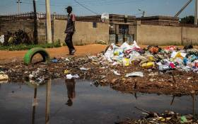 A man walks past a dump site in Ebumnandini on the West Rand, which residents complain is a health risk because they don't have dustbins. Picture: Kayleen Morgan/EWN