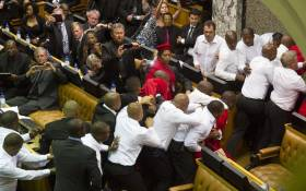 Members of the Parliament look on as members of the Economic Freedom Fighters, wearing red uniforms, clash with security forces during South African President's State of the Nation address in Cape Town on 12 February, 2015