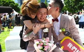 Shane Lin (C) is comforted by his partner Marc Yuan (R) and a friend during a wedding ceremony in Shinyi district in Taipei on 24 May 2019. Picture: AFP