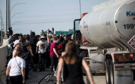 People react after a man drove a tanker truck into a crowd peacefully protesting the death of George Floyd on the I-35W bridge over the Mississippi River on May 31, 2020 in Minneapolis, Minnesota. Picture: AFP.