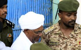 Omar al-Bashir is escorted before being driven in an armed convoy from the Kober prison to the prosecutor's office in North Khartoum on 16 June 2019.  Picture: AFP