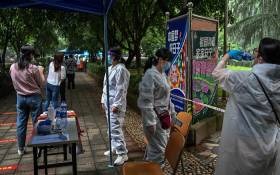 FILE: Workers stand next to Wuhan residents wearing face masks waiting in a line to be tested of COVID-19 in a neighbourhood in Wuhan, in China's central Hubei province on 15 May 2020. Picture: AFP