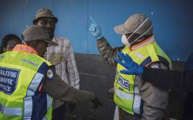 South African Metro policemen try to enforce distancing outside a supermarket in Hillbrow, Johannesburg, on 27 March 2020 where several dozens of customers are queuing for food without respecting the minimum safety distance. Picture: AFP