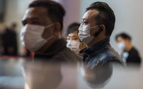 Passengers wearing masks queue at ticketing booths at a high-speed train station connecting Hong Kong to mainland China on 26 January 2020, as a preventative measure following a coronavirus outbreak which began in the Chinese city of Wuhan. Picture: AFP