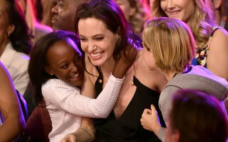 FILE: Actress Angelina Jolie hugs Zahara Marley Jolie-Pitt (L) and Shiloh Nouvel Jolie-Pitt (R) after winning the award for favourite villain in 'Maleficent' during Nickelodeon's 28th Annual Kids' Choice Awards in 2015. Picture: AFP.